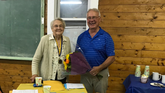 The Honourable Ross Wetmore, Minister of Agriculture, Aquaculture and Fisheries, presents Betty Lacey with a Certificate of Service for 76 years with the NBWI.